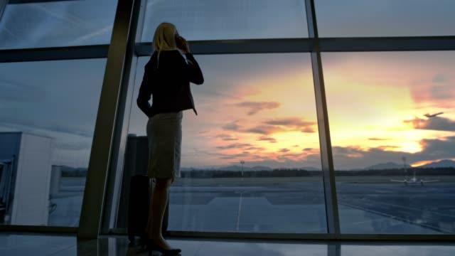 stockvideo's en b-roll-footage met zakenvrouw observeren van de zonsondergang door de glazen muur op de luchthaven, een telefoontje te nemen en weglopen - vliegveld vertrekhal