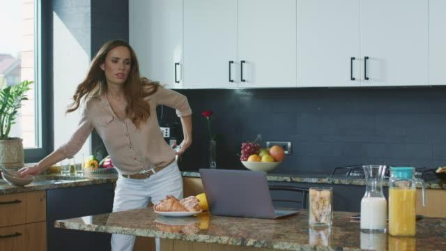 i̇ş kadını aceleyle kahvaltı hazırlıyor. meşgul anne çalışıyor. - sabah stok videoları ve detay görüntü çekimi