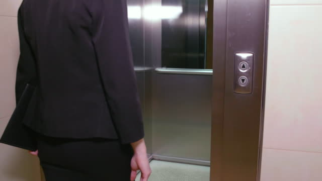 Business woman pushing button for calling elevator in business office corridor