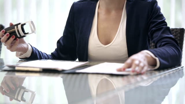 Business woman puts a seal on the contract. Close up video