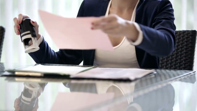 Business woman puts a seal on the contract. Slow motion