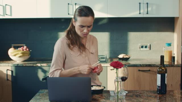 geschäftsfrau lesen nachrichten in der luxusküche. traurige frau bereitet sich darauf vor, sushi zu essen. - online dating stock-videos und b-roll-filmmaterial