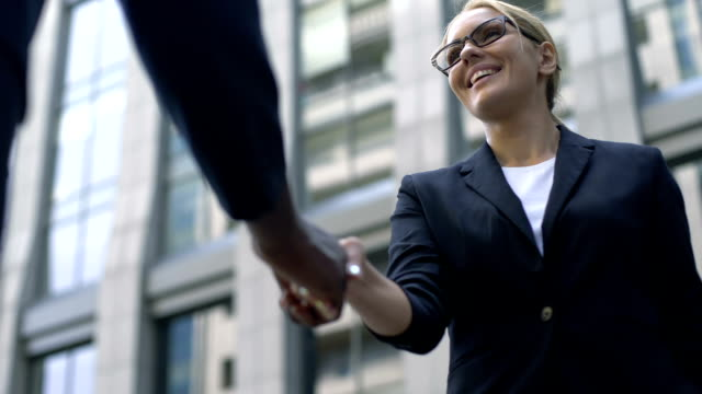 Business woman shaking hand with coworker, interpreter acquainting with client video