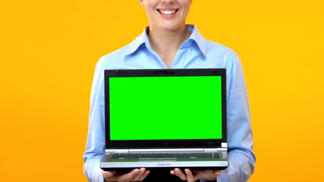 Business woman showing laptop with green screen, application advertisement