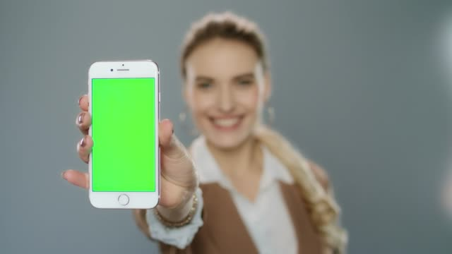business woman showing mobile phone with green screen in studio - mostrare video stock e b–roll