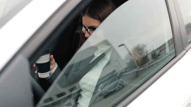 Business woman sits in her car in the driver's seat and opens a window to pick up coffee video