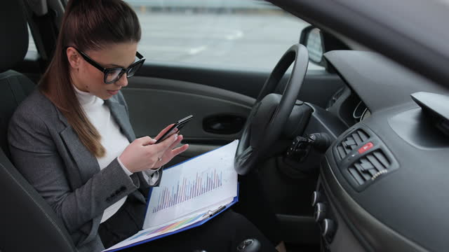 Business woman sits in her car in the driver's seat and takes pictures with her smartphone video