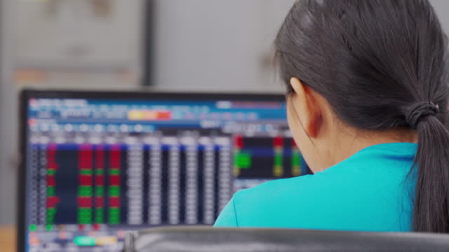 Business woman sitting font laptop computer with stock exchange on monitor,
