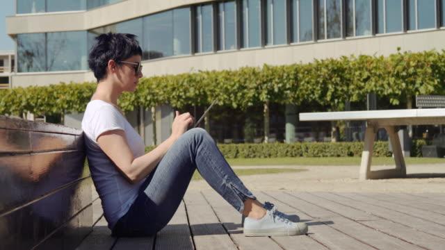 mujer de negocios sentado delante de un edificio de oficinas y trabajando en una tableta - vídeo