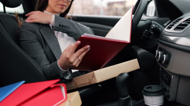 Business woman sitting in her car in the driver's seat and reviewing business documents video