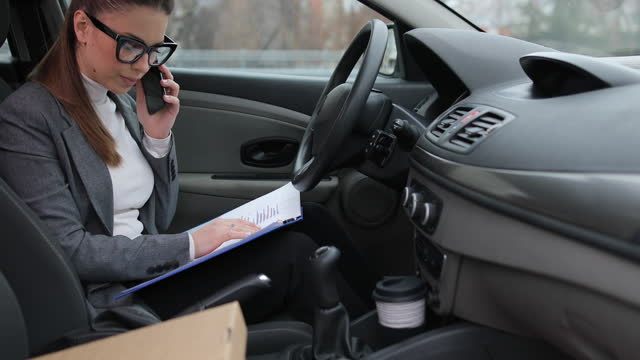 Business woman sitting in her car in the driver's seat and talking on a mobile phone with a business partner about the documents she holds in her lap video