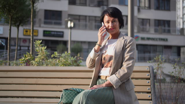 business woman sitting on a bench in the city and talking on the phone in the evening video