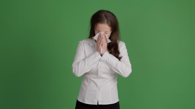 mujer de negocios estornudo en un fondo verde - vídeo