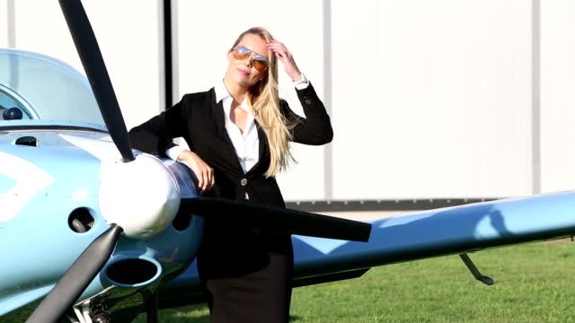 Business woman standing next to a small airplane video