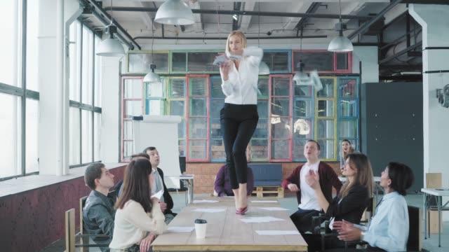 ビジネスウーマンはテーブルの上に立ち、踊り始め、お金や書類を散らします。彼女の同僚は彼女の成功を祝う。コーポレートパーティービジネスチーム。トレンディなオフィスインテリア� ビデオ