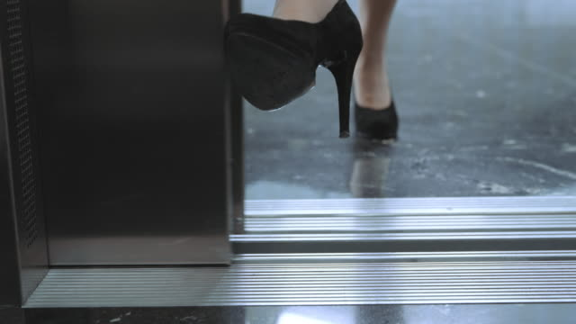 ds business woman stops the elevator door with her foot and enters - high heels stock videos & royalty-free footage