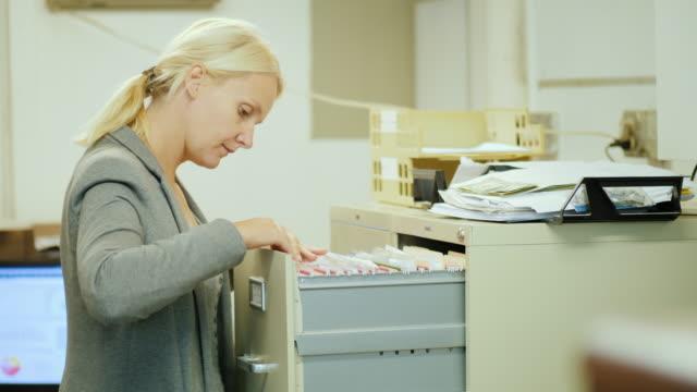 vídeos y material grabado en eventos de stock de mujer de negocios tiene una carpeta con documentos de un cajón en estilo retro - suministros escolares