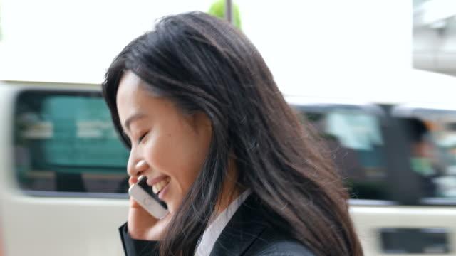 vidéos et rushes de femme d'affaires parler sur smartphone - seulement des japonais