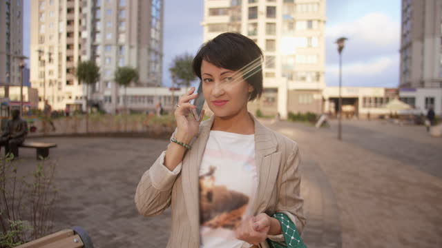 Business woman talking on the phone on the street and smiling, negotiates a deal video