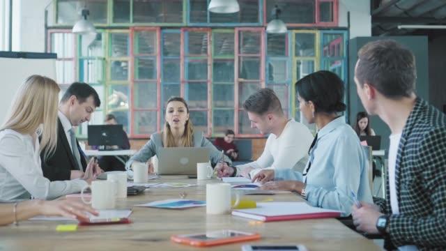 Business-Frau-Teamleiter beginnt sich mit Mitarbeitern zu treffen, setzt sich an den Tisch und öffnet den Laptop. Kreative Büro-Interieur. Co-Working Startup Team. Büroleben – Video