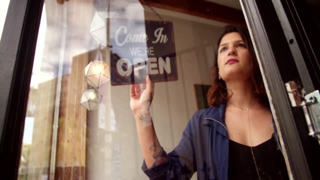 geschäft frau drehen geschlossen schild an der tür des kaffee shop - geschlossen allgemeine beschaffenheit stock-videos und b-roll-filmmaterial