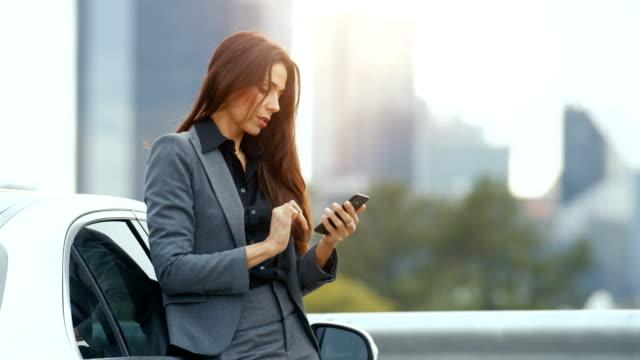 stockvideo's en b-roll-footage met zakelijke vrouw toepassingen smartphone terwijl leunend op haar premium klasse auto. grote stad met wolkenkrabbers in de achtergrond. - woman very rich