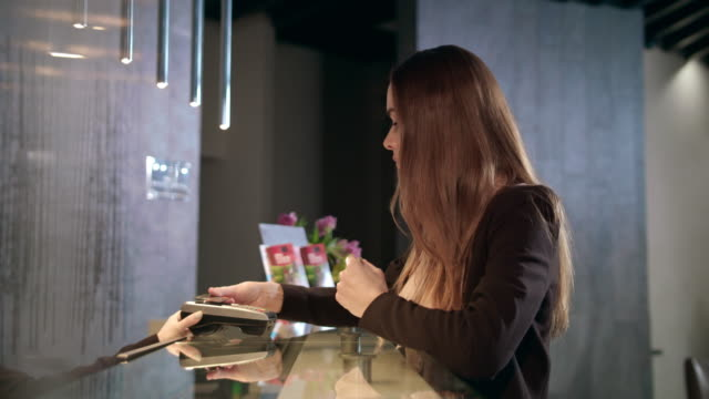 vídeos de stock e filmes b-roll de business woman using credit card for mobile payment in hotel - paying with card contactless