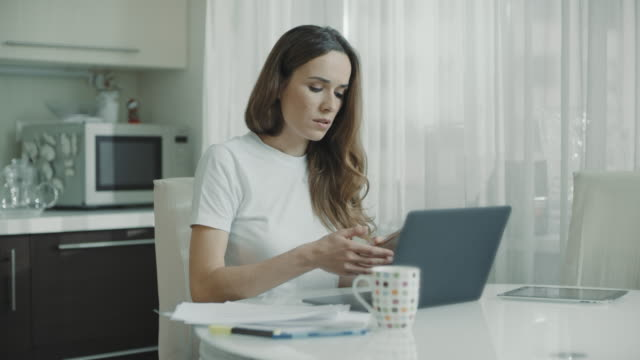 Business woman using laptop computer at home. Professional call mobile phone