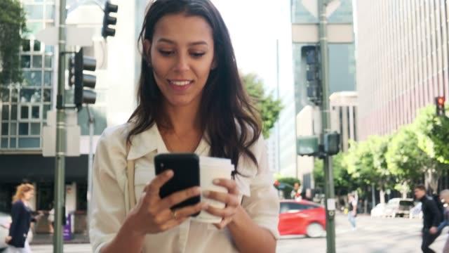 stockvideo's en b-roll-footage met zakelijke vrouw met behulp van slimme telefoon en het drinken van koffie op de weg - gewone snelheid