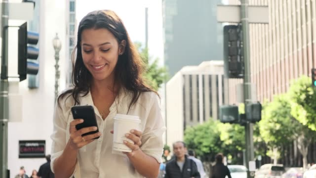business woman using smart phone and drinking coffee on the go - digital mobile consumption video stock e b–roll