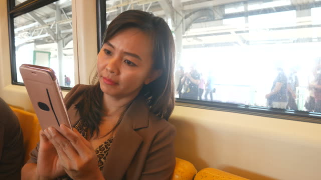 business woman using smartphone on city train video