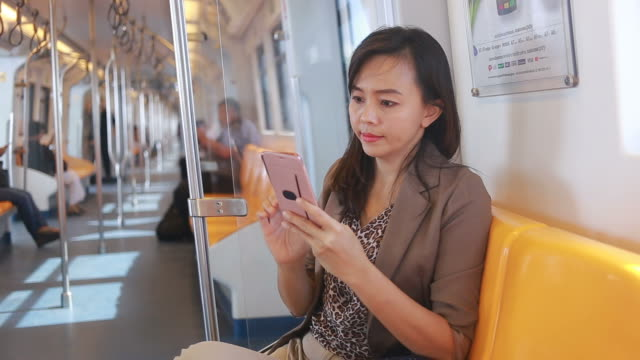 business woman using smartphone on city train business Asian woman using smartphone on city  train subway train stock videos & royalty-free footage