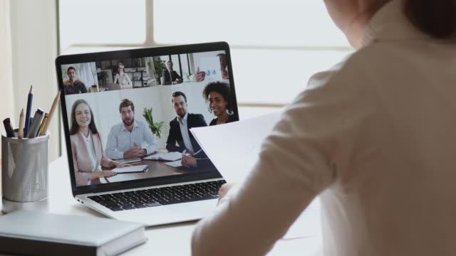 ウェブカメラで多様なオフィスチームを呼び出すビジネスウーマンビデオ会議 - 人里離れた点の映像素材/bロール