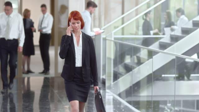ds donna d'affari camminando lungo il corridoio - carrellata video stock e b–roll