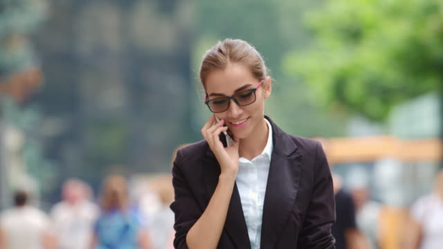 Business woman walking down the street towards the camera and speaking phone video