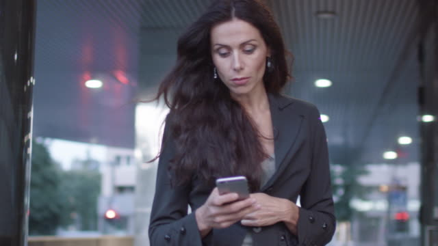 Business Woman Walking on Streets of Business District Holding Mobile Phone. Slow Motion video