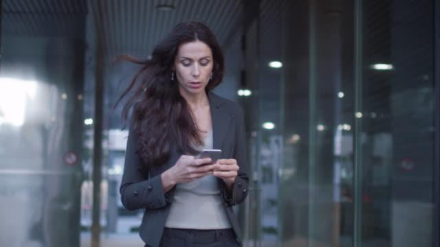 stockvideo's en b-roll-footage met zakenvrouw lopen op de straten van zakendistrict bedrijf van de mobiele telefoon. slow motion - business woman phone