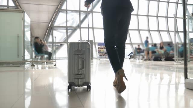 stockvideo's en b-roll-footage met zakenvrouw wandelen met reistas in de terminal van de luchthaven of de metro - zakenreis