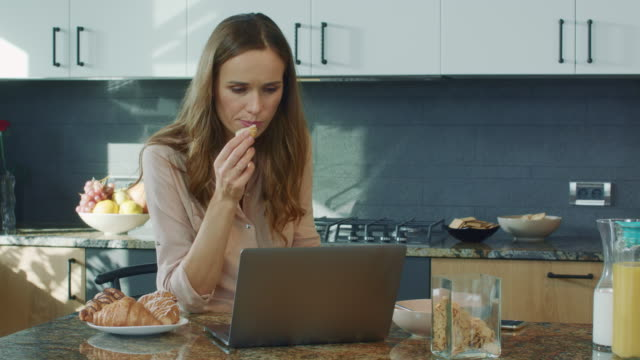 Business woman watching video in luxury kitchen. Woman getting bad news.