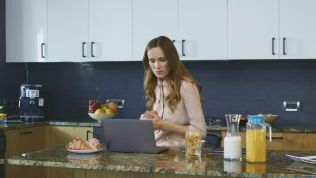 affärs kvinna tittar på video på datorn. koncentrerad kvinna som dricker kaffe. - looking inside inside cabinet bildbanksvideor och videomaterial från bakom kulisserna