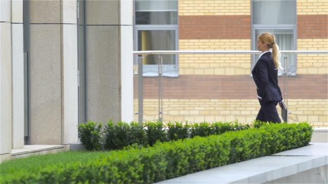 affärskvinna med surfplatta går runt kontorsbyggnad. slowmotion - djurarm bildbanksvideor och videomaterial från bakom kulisserna
