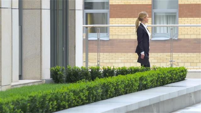 affärskvinna med surfplatta går runt kontorsbyggnad. slowmotion, ut ur byggnaden - djurarm bildbanksvideor och videomaterial från bakom kulisserna