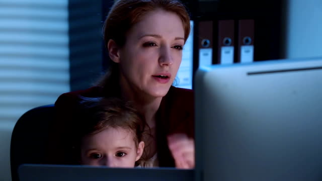 Business woman working at the computer late at night with a baby on her lap. video