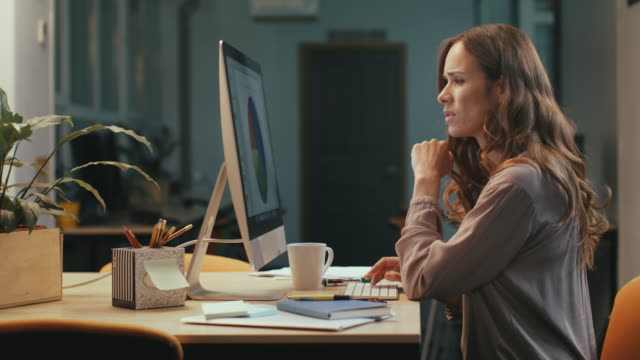 Business woman working late in office. Serious woman finding mistake.