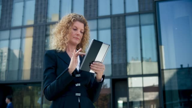 DS Business woman working on her digital tablet in front of a modern business building