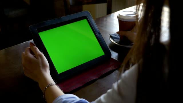 business frau arbeiten mit tablet-pc mit greenscreen und kaffee trinken - tablet mit displayinhalt stock-videos und b-roll-filmmaterial