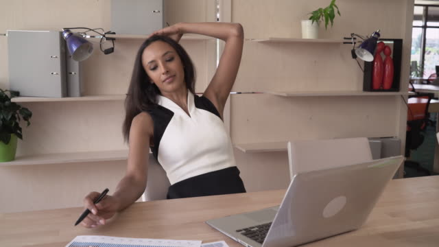 Business woman working with financial documents have a little break to fix her hair video