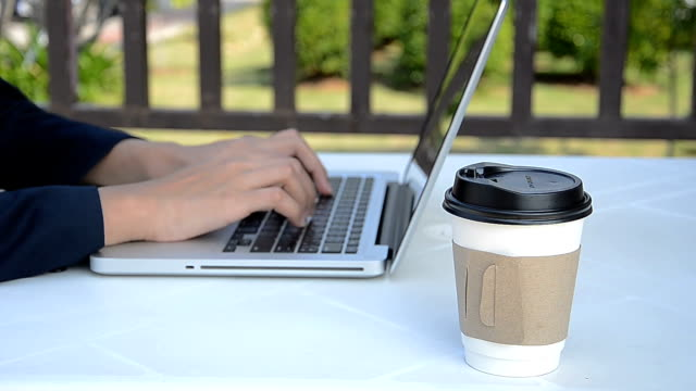 Business woman working with  laptop (notebook) and drinking hot coffee. video