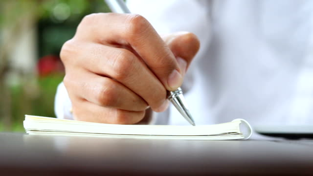 Business woman write on notebook outdoor in coffee shop. video