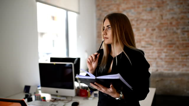 Business woman writing down to notebook plan for near future